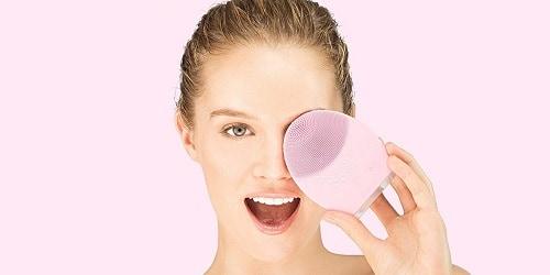 Dit is een foto waar een vrouw een elektrische gezichtsborstel vasthoudt. Deze elektrische gezichtsborstel is roze van kleur en van silicone materiaal gemaakt.