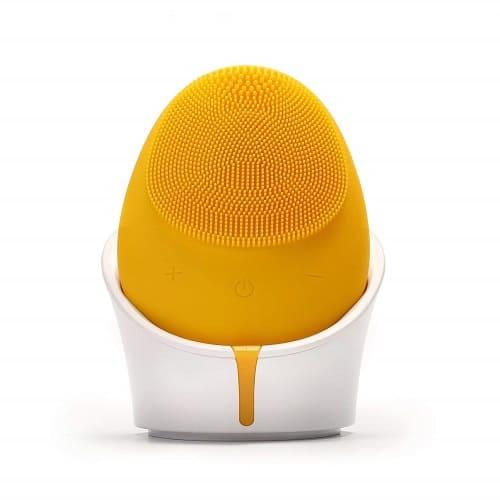 Dit is een foto van een elektrische gezichtsborstel van silicone kwaliteit. Deze borstel staat in een houder waar men gemakkelijk een usb lader in stopt.