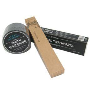 Dit is een foto waar een aantal charcoal producten op worden afgebeeld zoals; charcoal poeder, charcoal tandpasta en een bamboo tandenborstel.