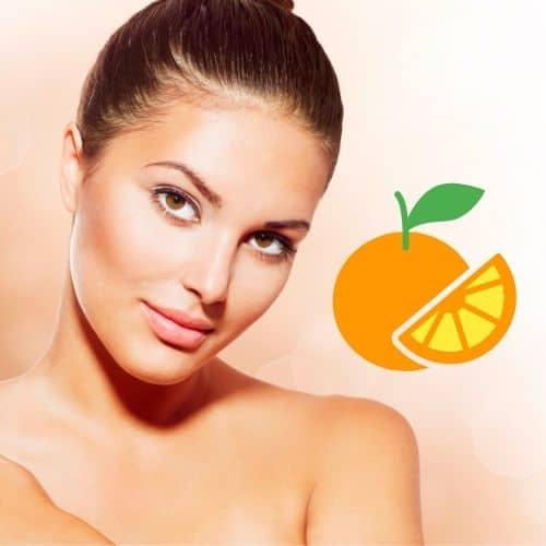Op deze foto wordt een gezicht van een vrouw afgebeeld en een sinaasappel. (vitamine c serum)
