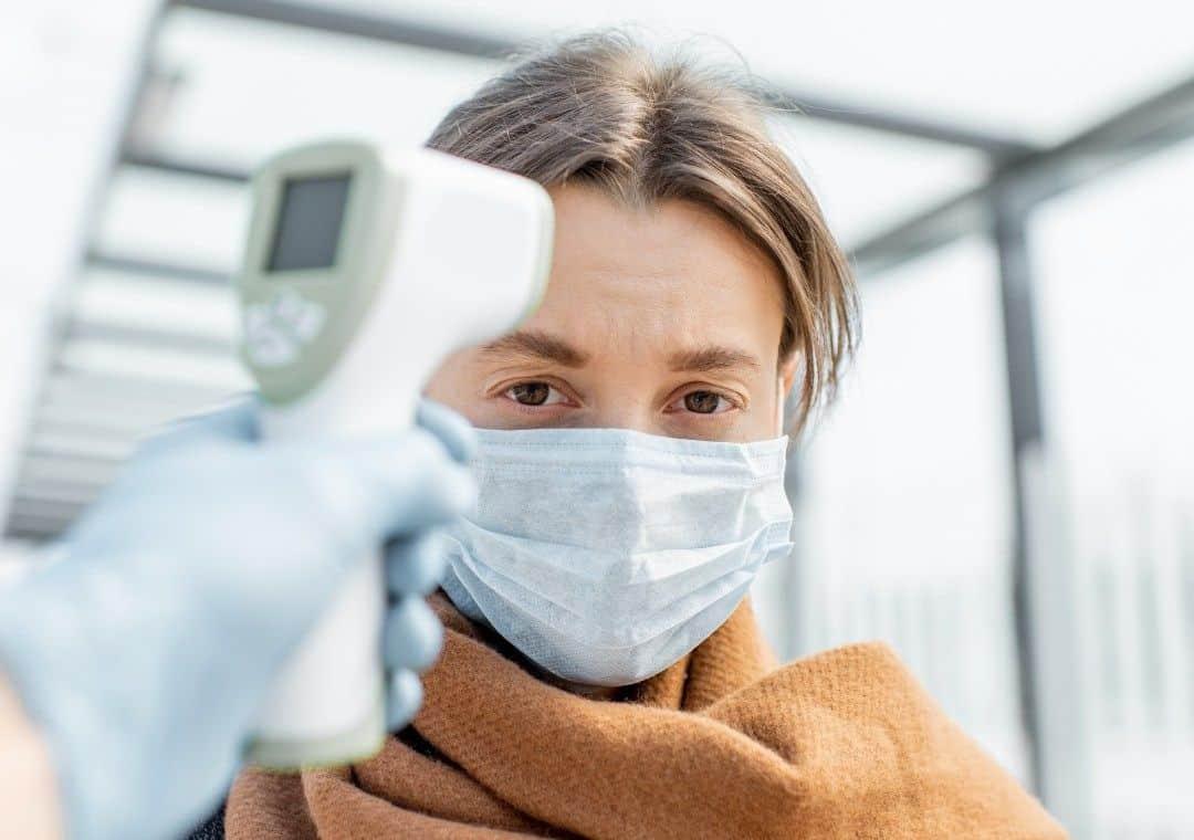 Hier wordt een vrouw gemeten met een infrarood thermometer. De vrouw wordt gemeten op temperatuur in het openbaar. Men richt op haar voorhoofd.