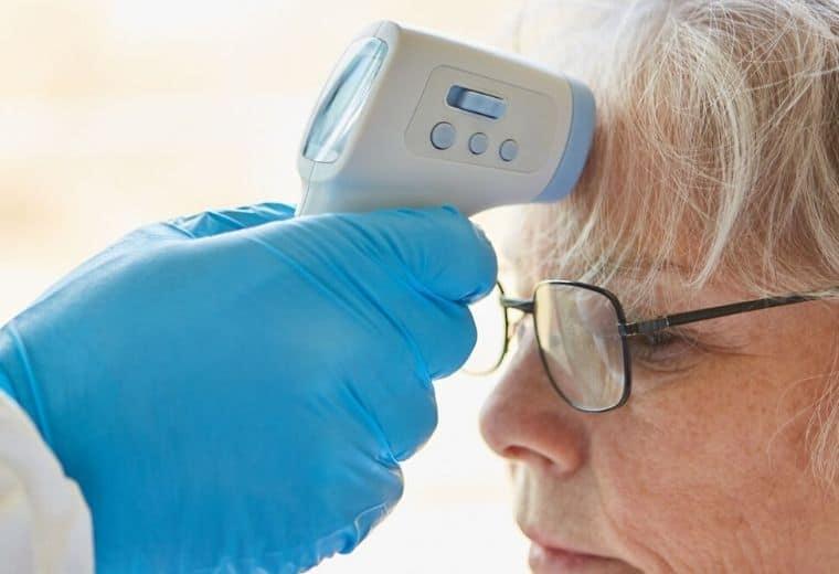 De temperatuur van de vrouw wordt gemeten met een infrarood thermometer. Dit is een non contact infrarood thermometer. Men richt op het voorhoofd.