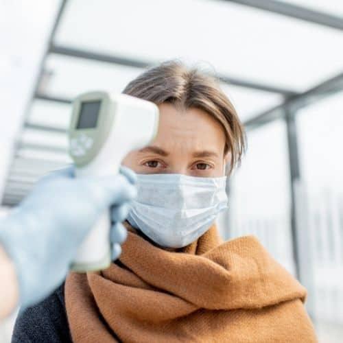 De lichaamstemperatuur van deze vrouw wordt gemeten met een infrarood thermometer. Dit is een non contact infrarood thermometer. Zij wordt gemeten in het openbaar.