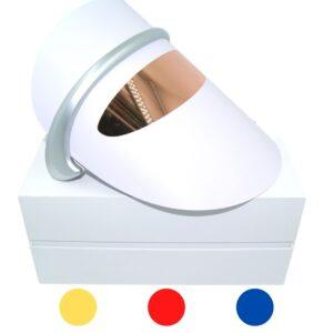 Hier wordt een lichttherapie photon masker afgebeeld inclusief verpakking. Het lichttherapie photon masker heeft 3 kleuren, rood - blauw - geel en wordt gebruikt om huidproblemen te behandelen.