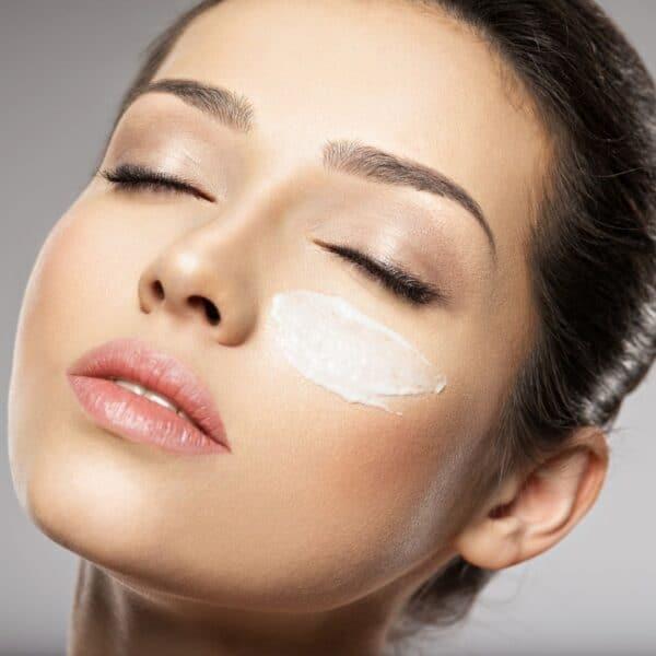 Dit is een foto van een vrouw die collageen crème op haar gezicht smeert. Collageen crème smeert men op de huid.
